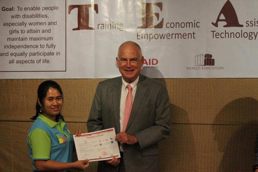 AfA-Präsidenting Phokham Douangdala nimmt aus den Händen von US-Botschafter Daniel A. Clune die Bestätigungsurkunde entgegen
